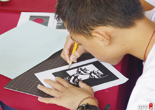 A participant of the kirie workshop orking on his paper cut.
