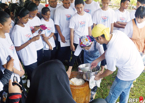 Visitors look on during the preparation of mochi.